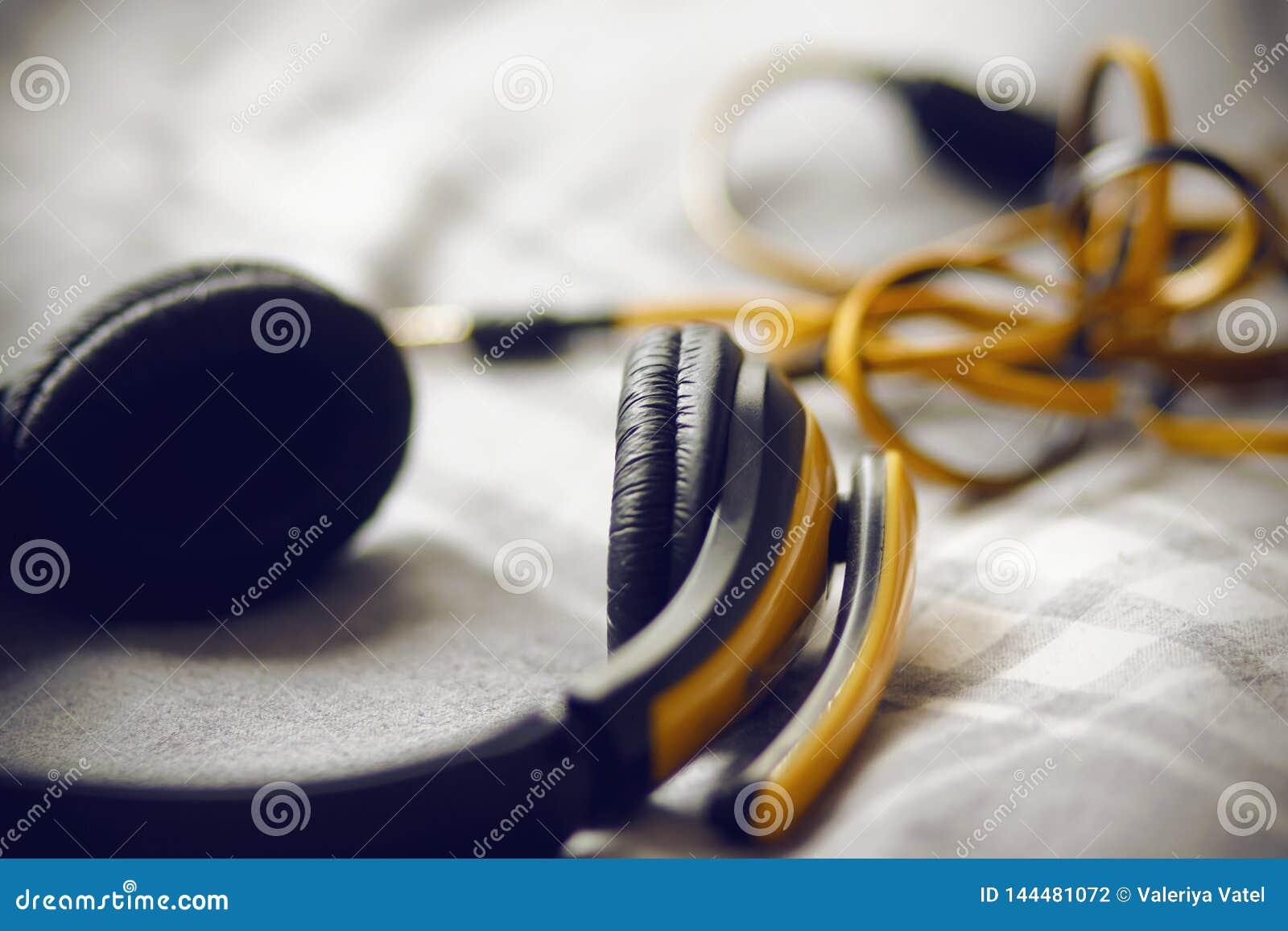 De grote gele hoofdtelefoons liggen op een grijze plaid