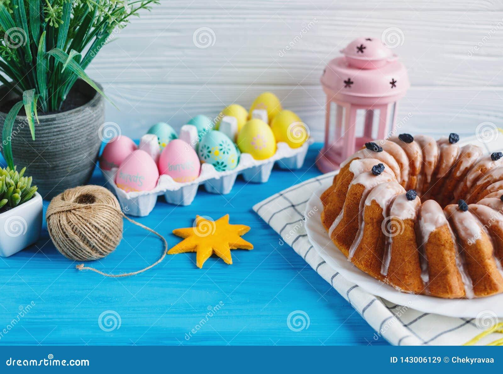 De grote plaat met cake en hand schilderde kleurrijke eieren, op handdoek op blauwe achtergrond Sluit omhoog Decoratie voor Pasen