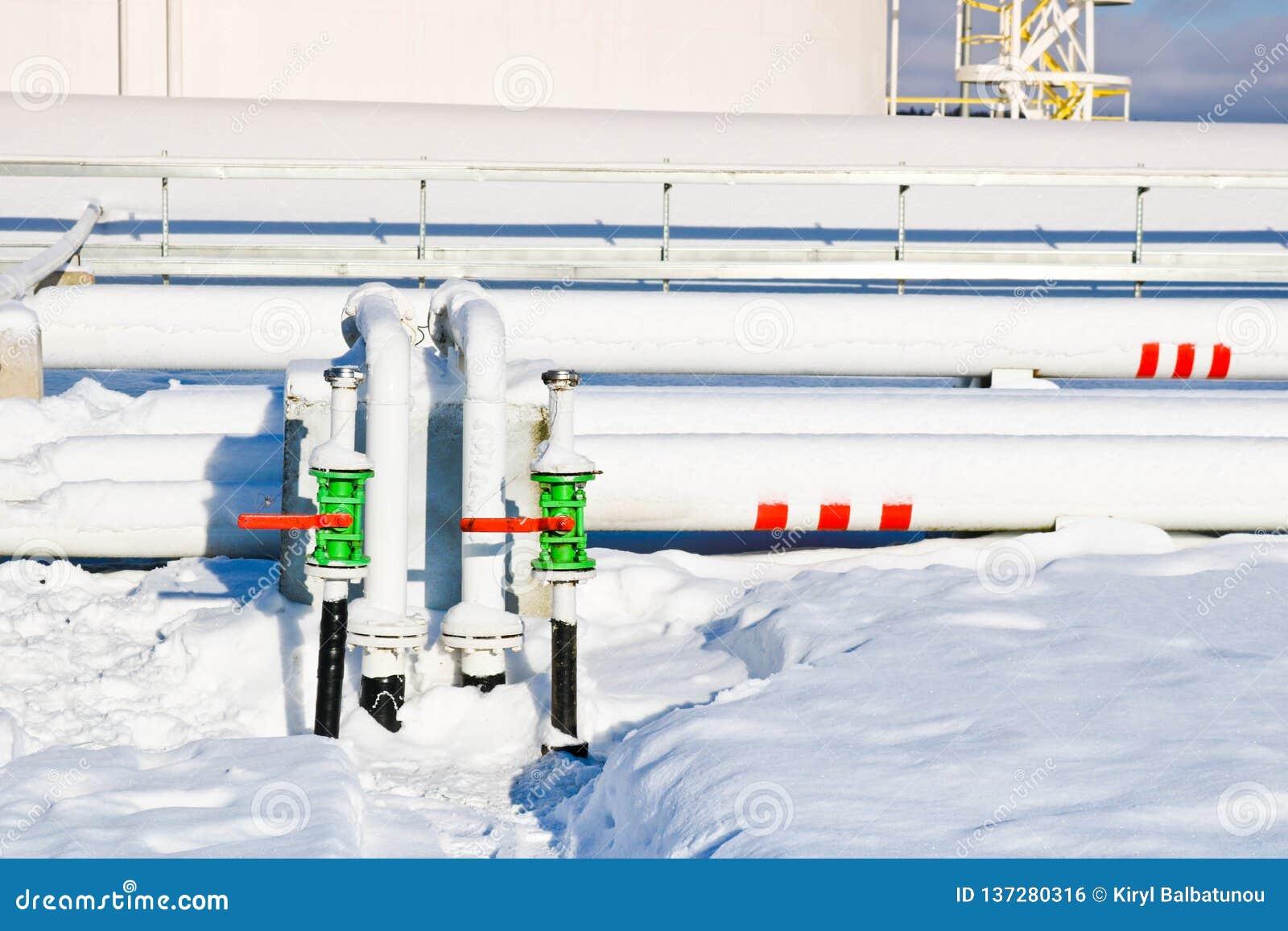 De grote witte industriële tanks van het ijzermetaal voor opslag van brandstof, benzine en diesel en pijpleiding met kleppen en f