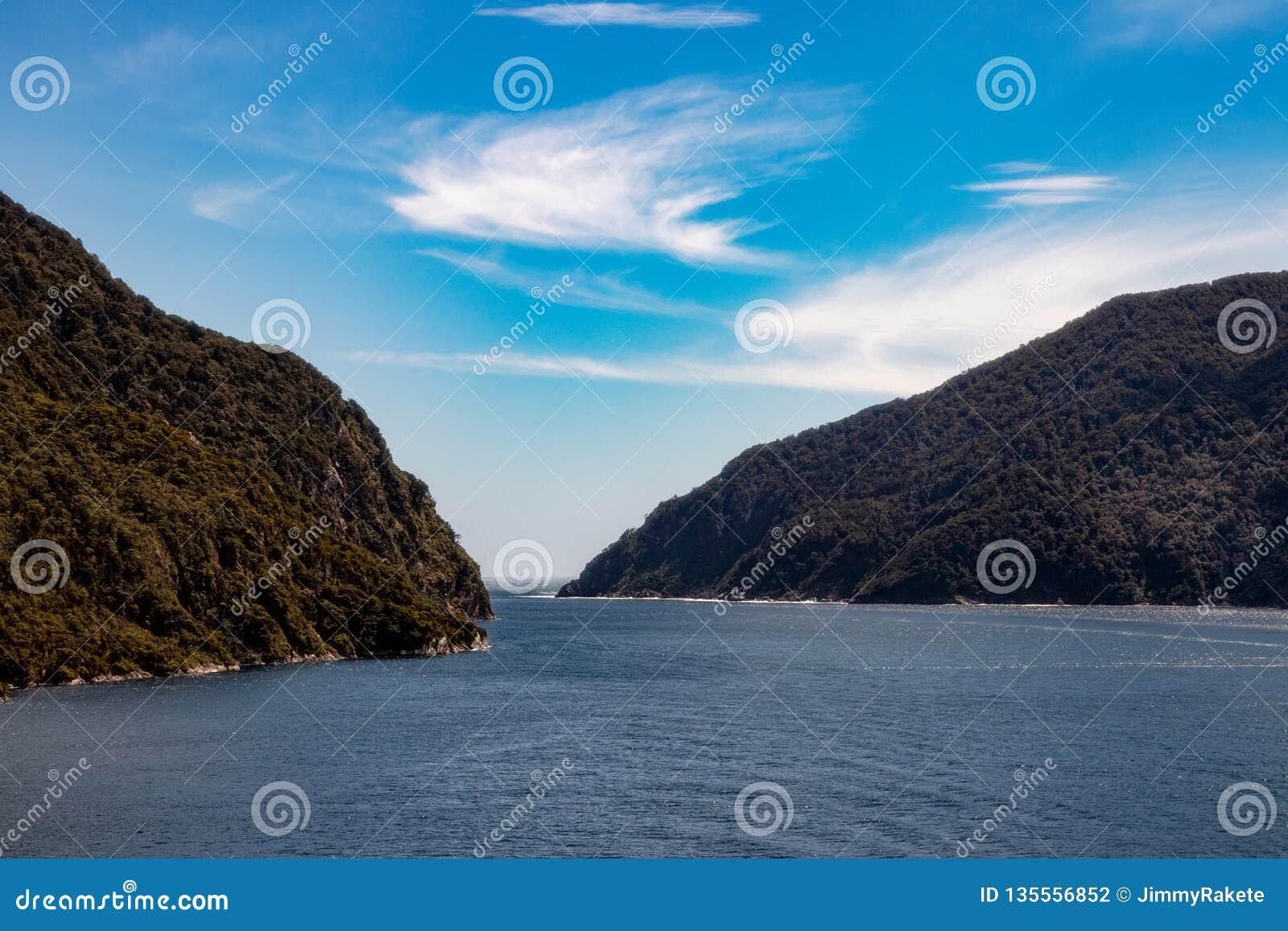 De härliga dunkla ljuden i Fjordland, Nya Zeeland, med en blå himmel och trevliga moln