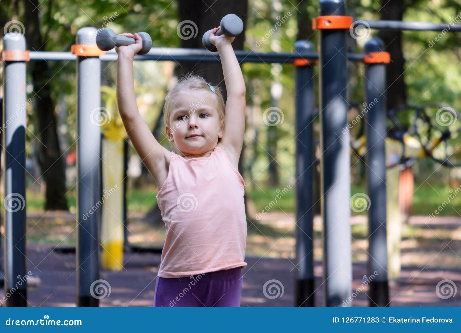 De höga lönelyfthantlarna för barn Lite går flickan med blont hår in för sportar