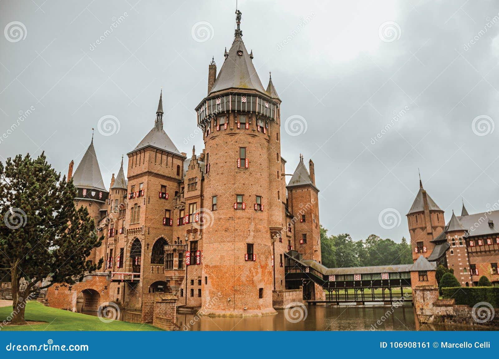 De Haar Roszujący z cegłą góruje blisko Utrecht, wodna fosa i gazonu ogród na deszczowym dniu,