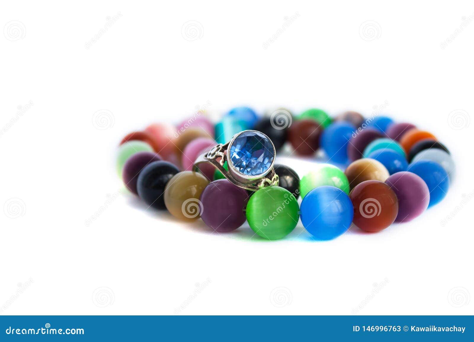 De halsband van het het oogkwarts van de kat en armband, selectieve nadruk op witte geïsoleerde achtergrond Kleurrijke edelstenen