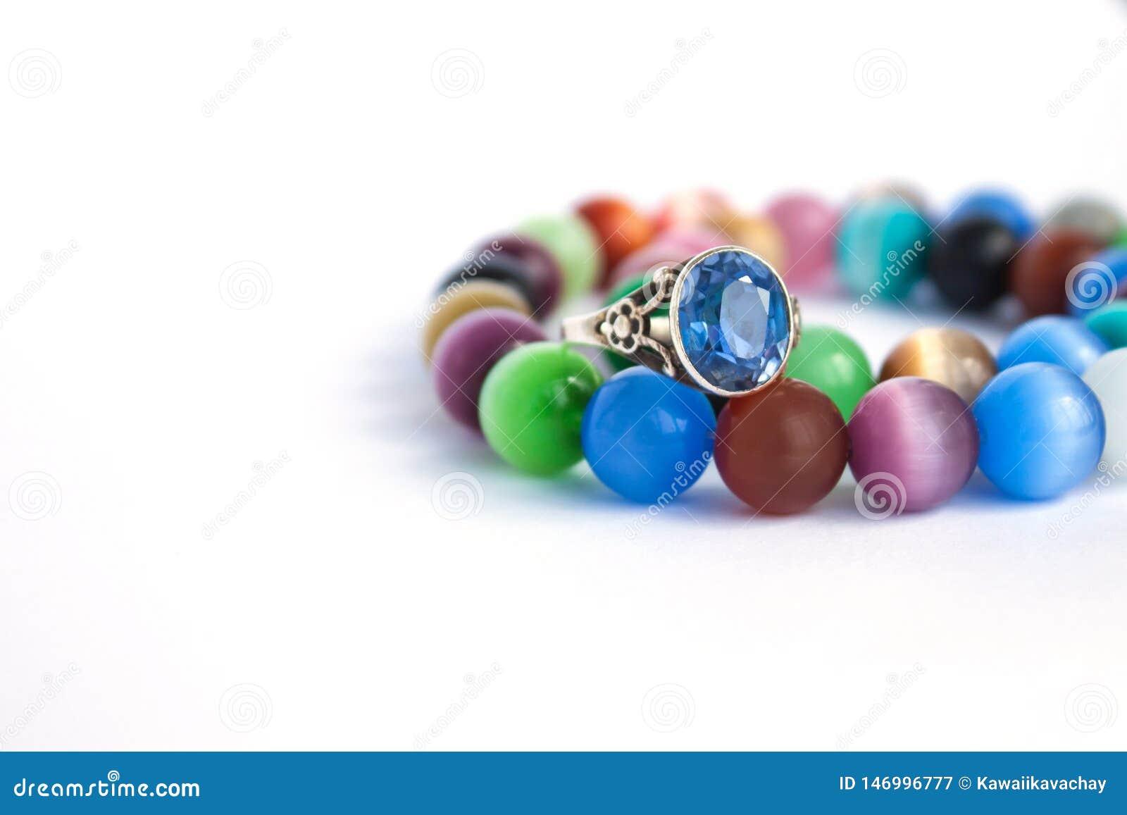 De halsband van het het oogkwarts van de kat en armband, selectieve nadruk op witte ge?soleerde achtergrond Kleurrijke edelstenen