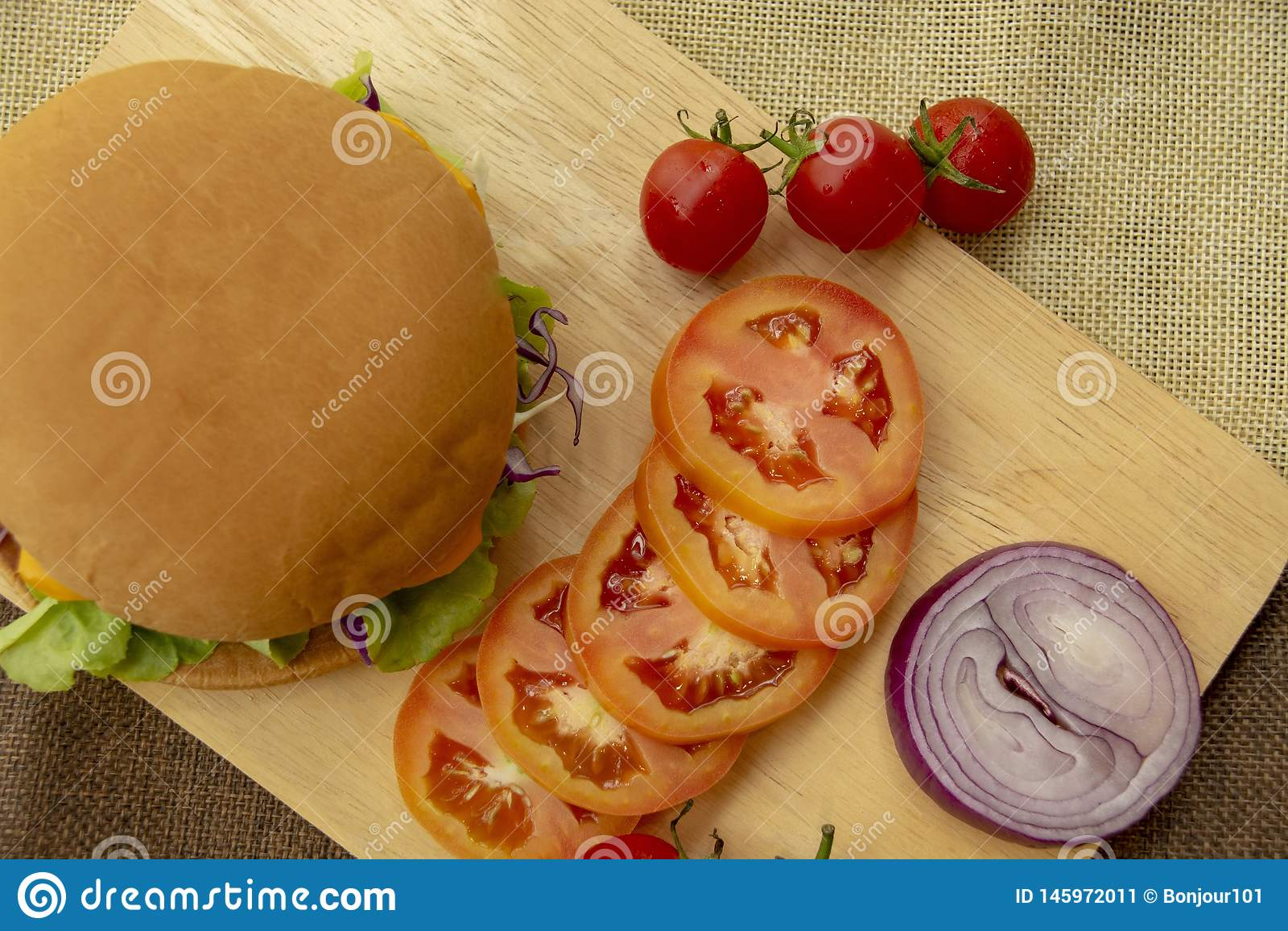 De hamburger wordt voorbereid met geroosterde varkensvlees, kaas, tomaten, sla en uien op een rechthoekige houten vloer