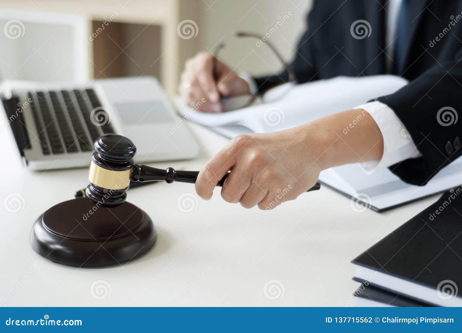 De hamer van de de holdingsrechtvaardigheid van de bedrijfsadvocaathand op kantoor met laptop, boek en documenten
