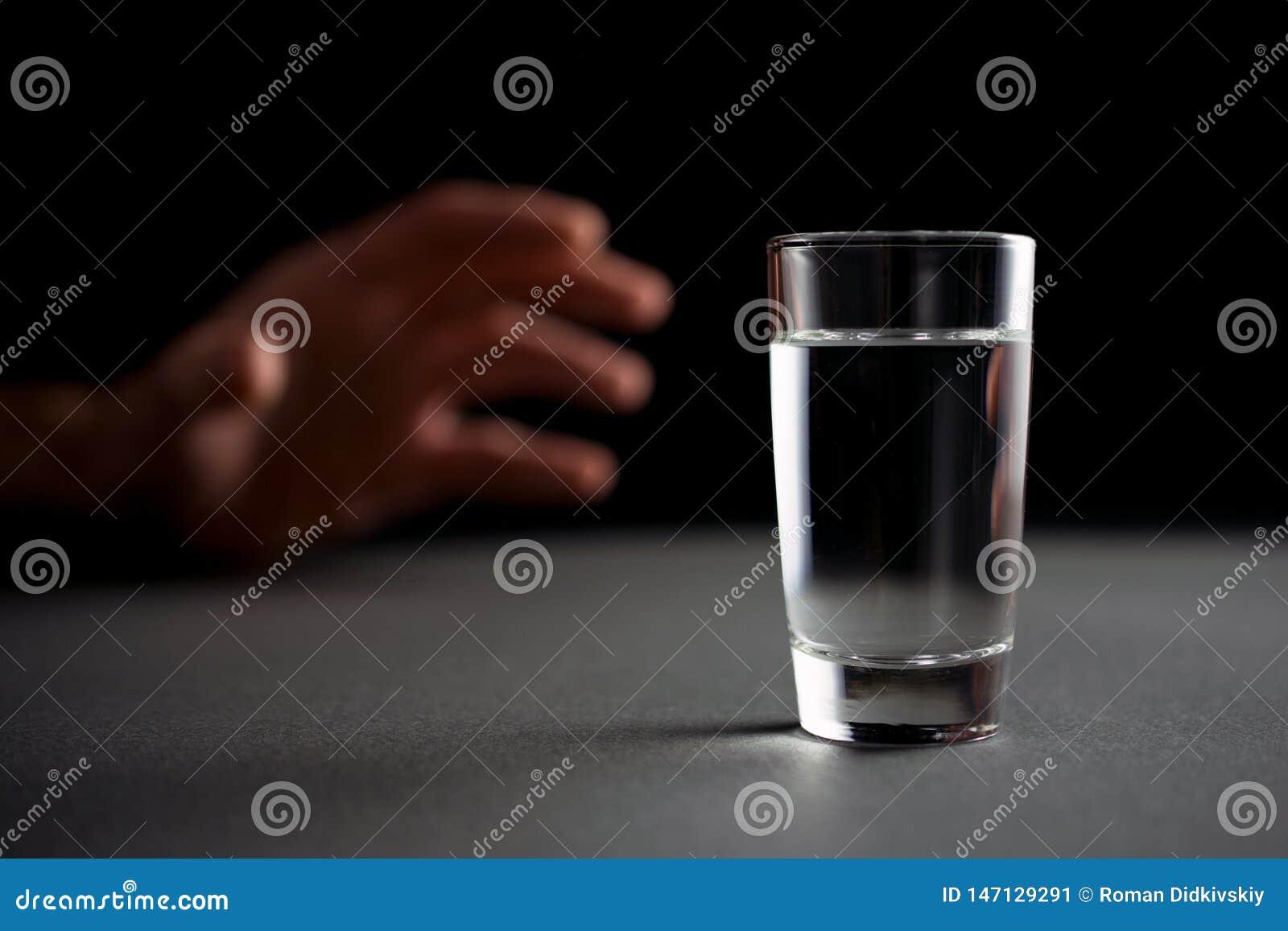 De hand bereikt voor een glas wodka