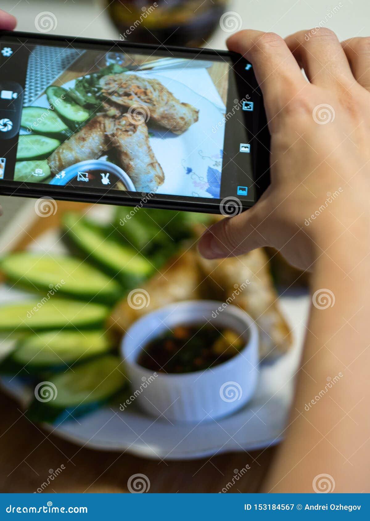 De hand die een smartphone gebruiken aan foto braadde Vietnamese pannekoeken