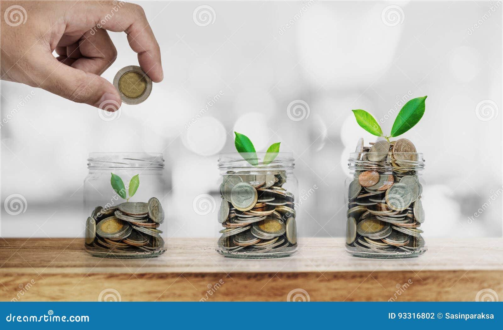 De hand die muntstuk in glasflessen zetten met installaties gloeien, die geld, investering besparen en bezuinigt concept