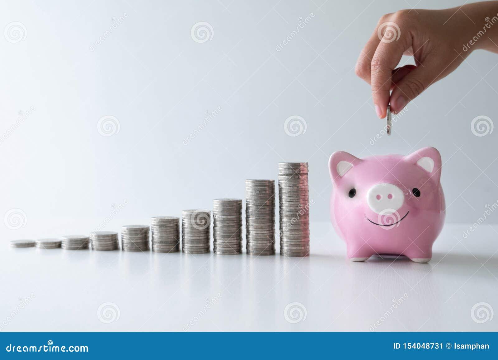 De hand die muntstuk in roze spaarvarken met muntstukkengrafiek zetten, voert startzaken aan succes op, die geld voor toekomstig
