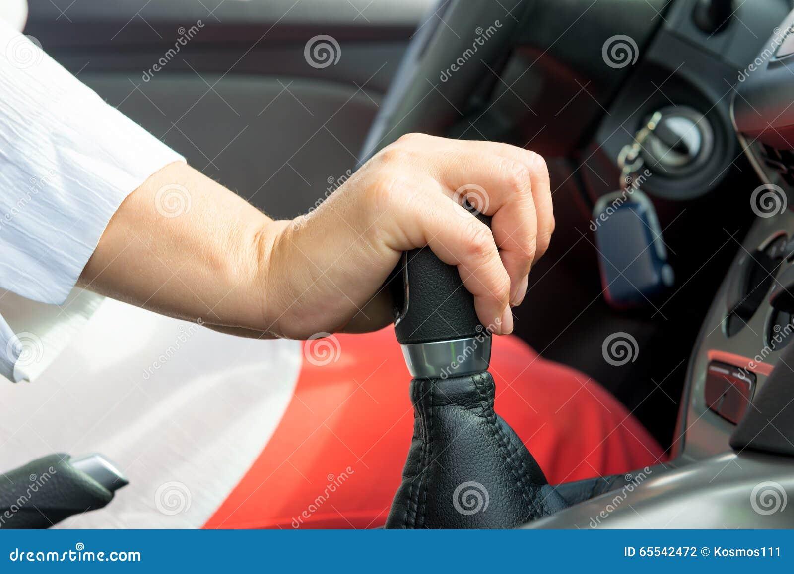 De hand die van de vrouw de verschuivingshefboom in een auto houden