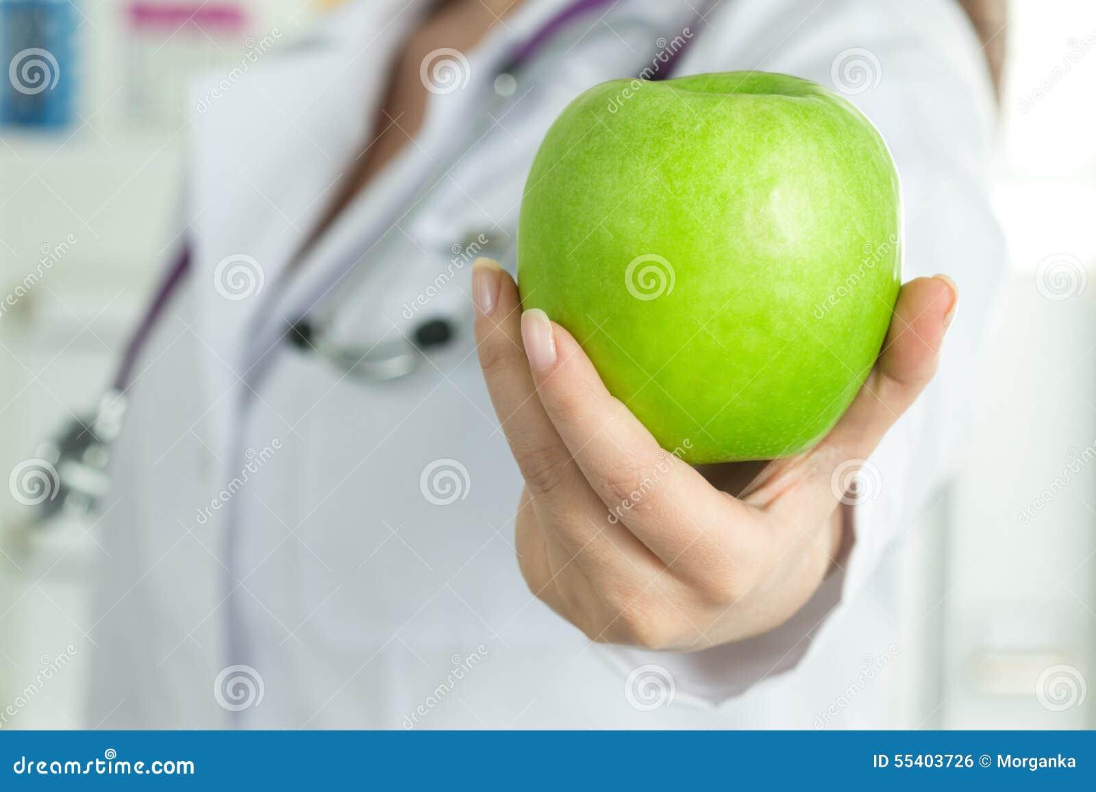 De hand die van de vrouwelijke arts verse groene appel geven