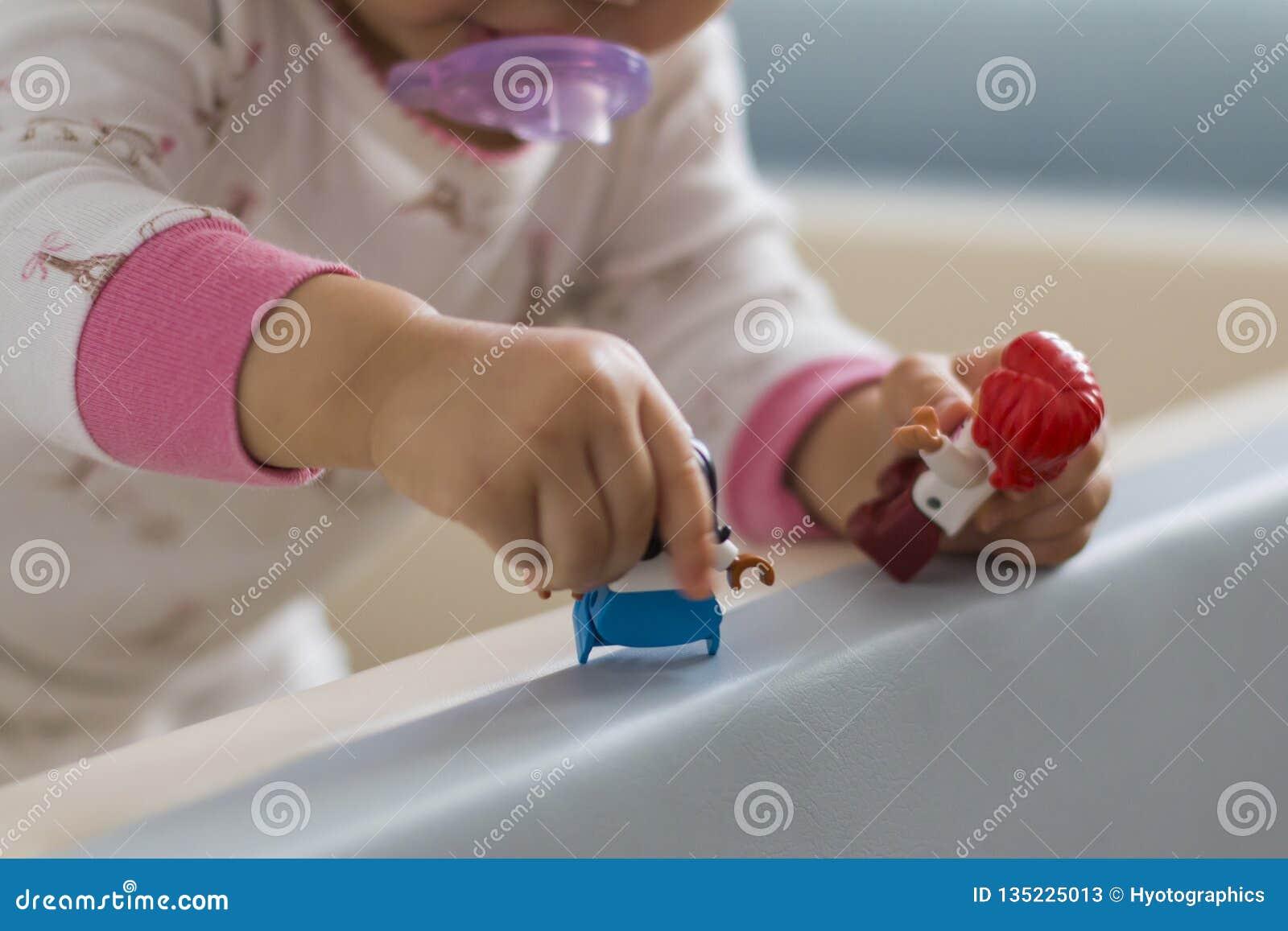 De hand die van een baby een stuk speelgoed houden