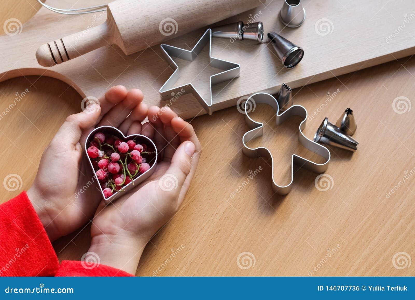 De hand die van het meisje traditionele feestelijke koekjes maken Het bakken met liefdeconcept Moederdag, de Dag van Vrouwen, de
