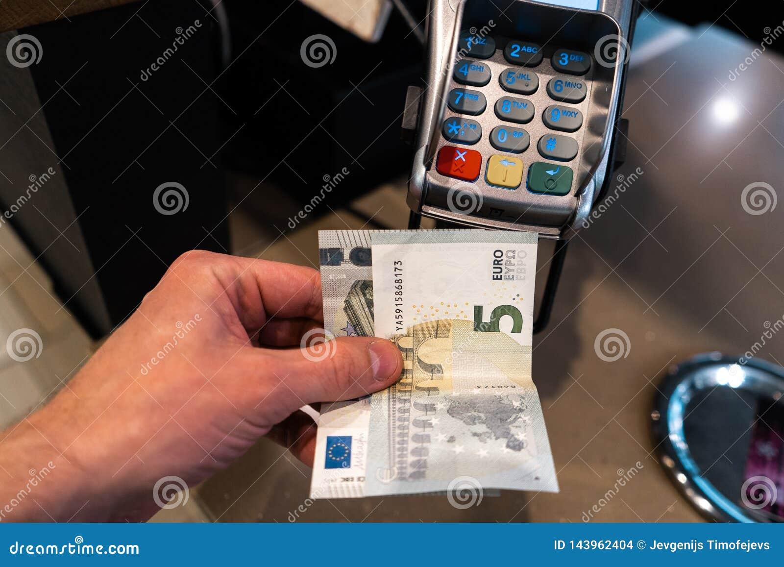 De hand die van mensen EURO bankbiljetten houden dichtbij een betaling eindpos in een koffie
