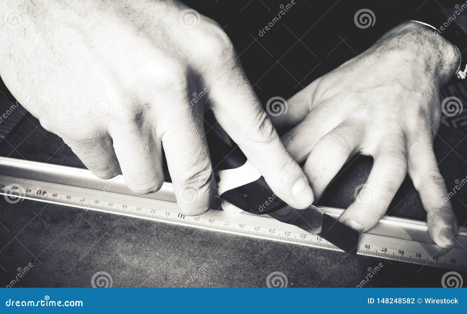 De hand die van de persoon met een heerser werken