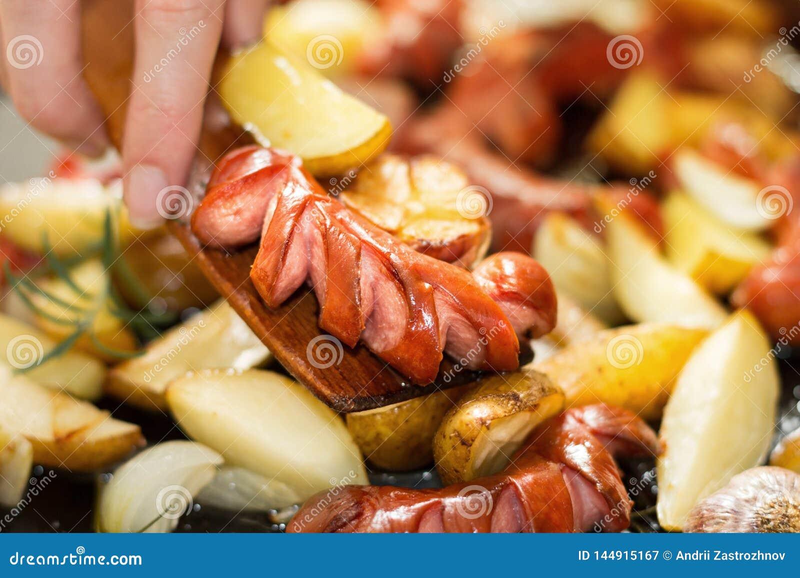 De hand, een houten spatel giet een hoog-calorie en een vettig diner Horizontaal beeld