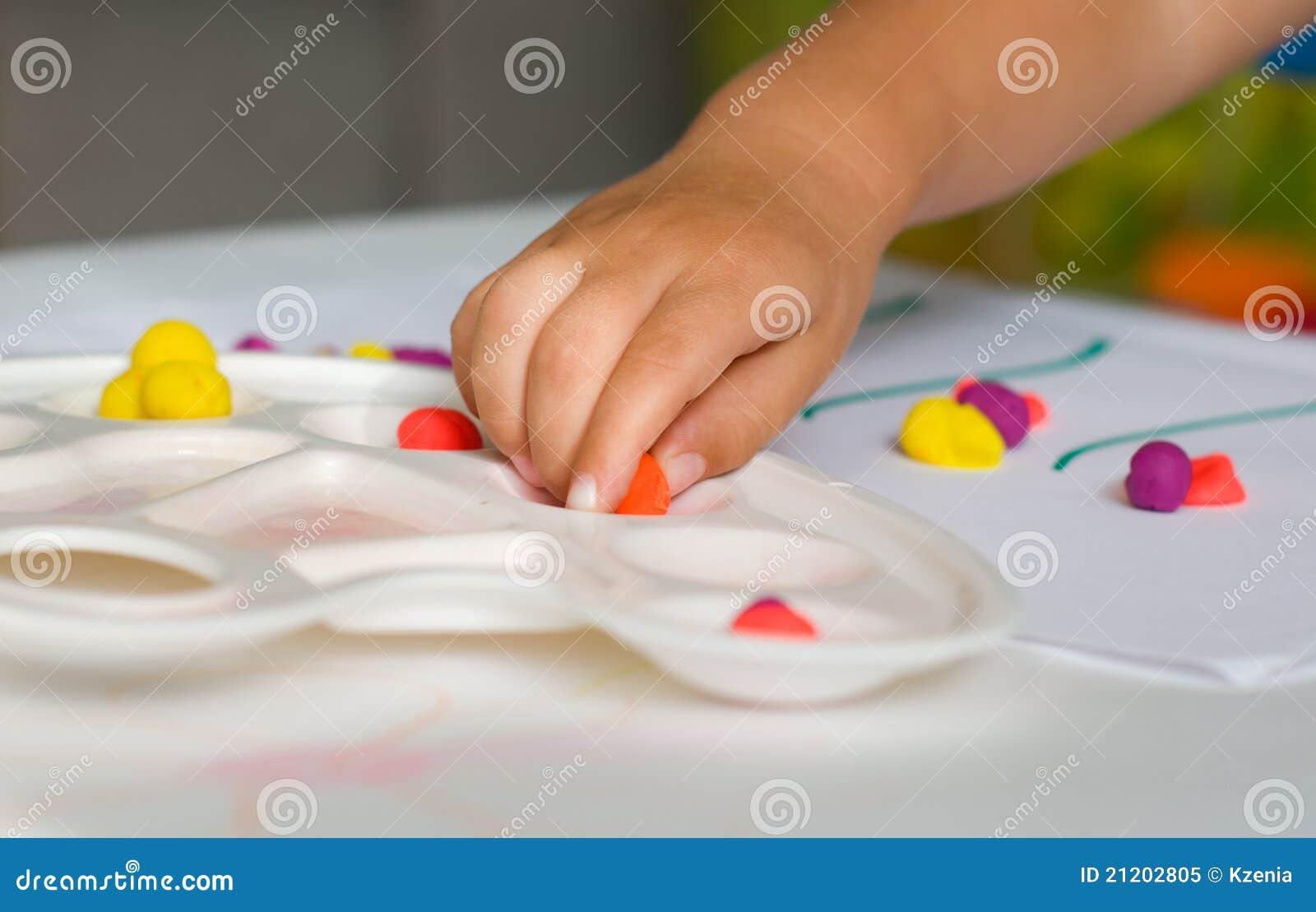 De hand en plasticine van de baby