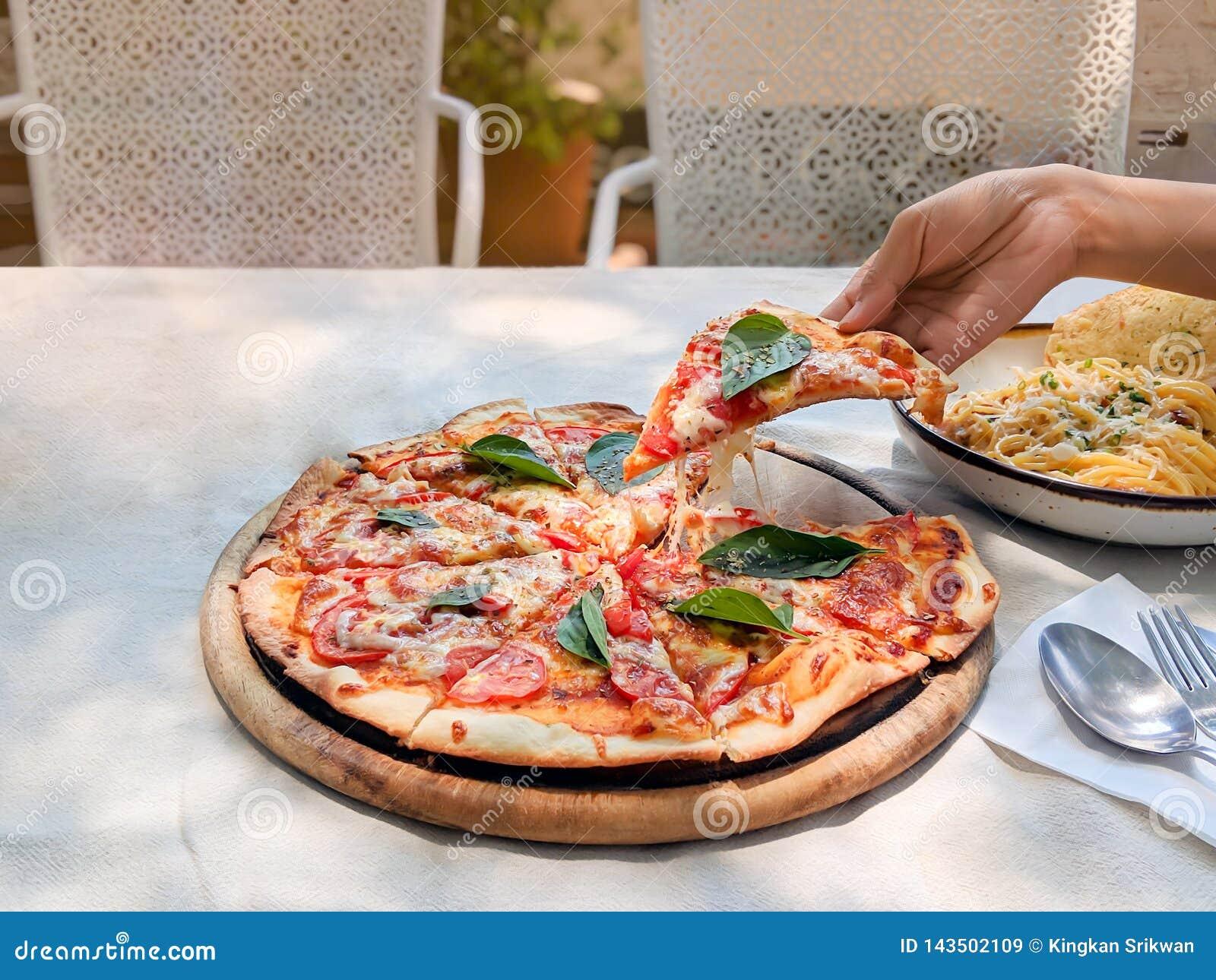 De hand houdt en trekt een plak van pizzamargherita uit het dienblad
