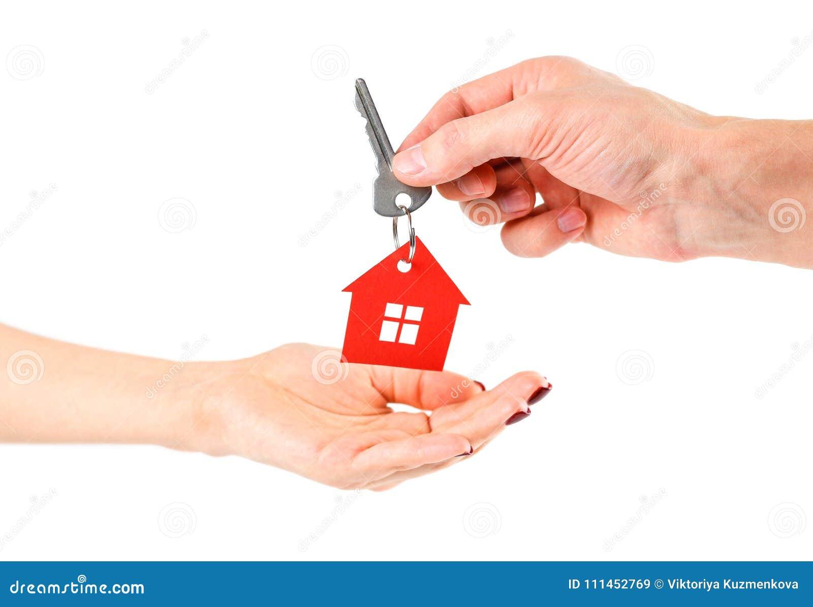 De hand houdt de sleutels met het rode huis keychain Aankoop van