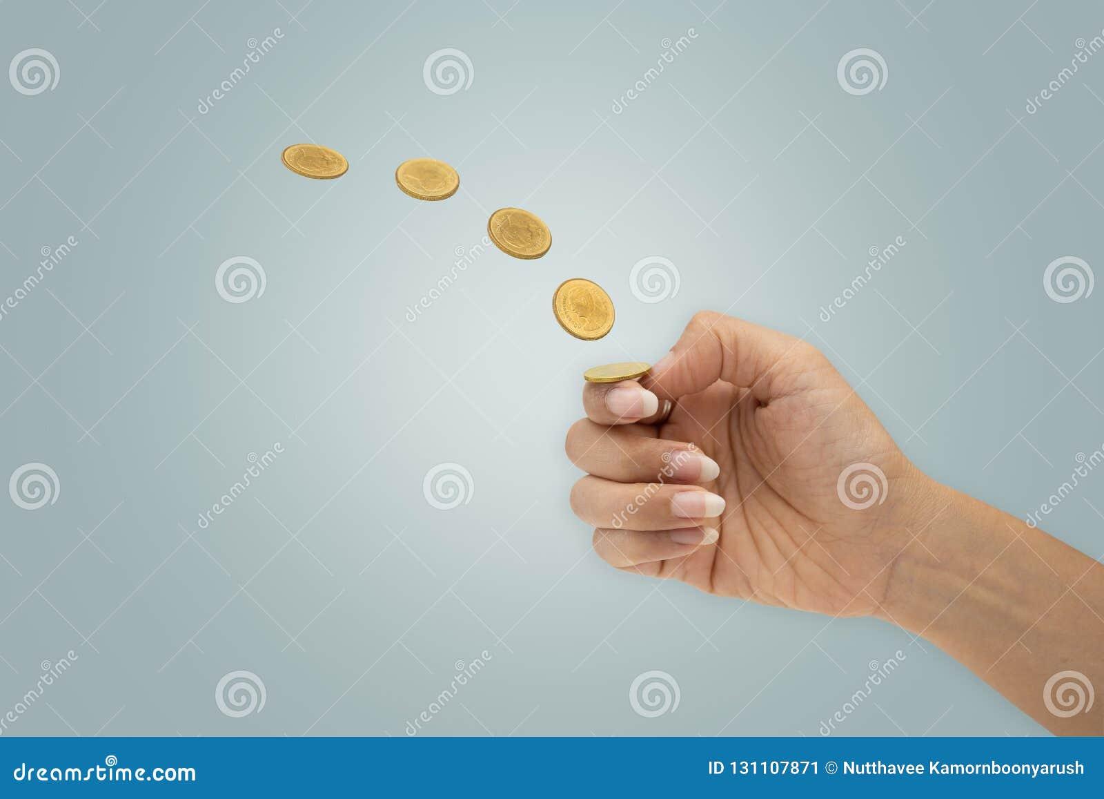 De hand knipt een muntstuk weg op blauwe achtergrond wordt geïsoleerd die
