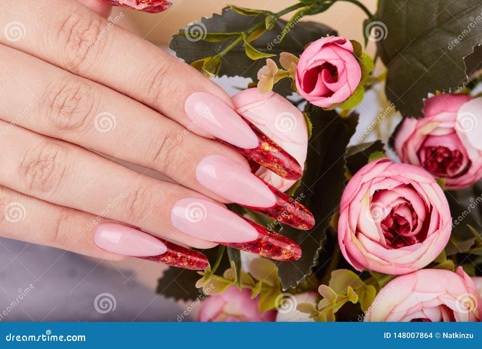 De hand met het lange rode kunstmatige Frans manicured spijkers