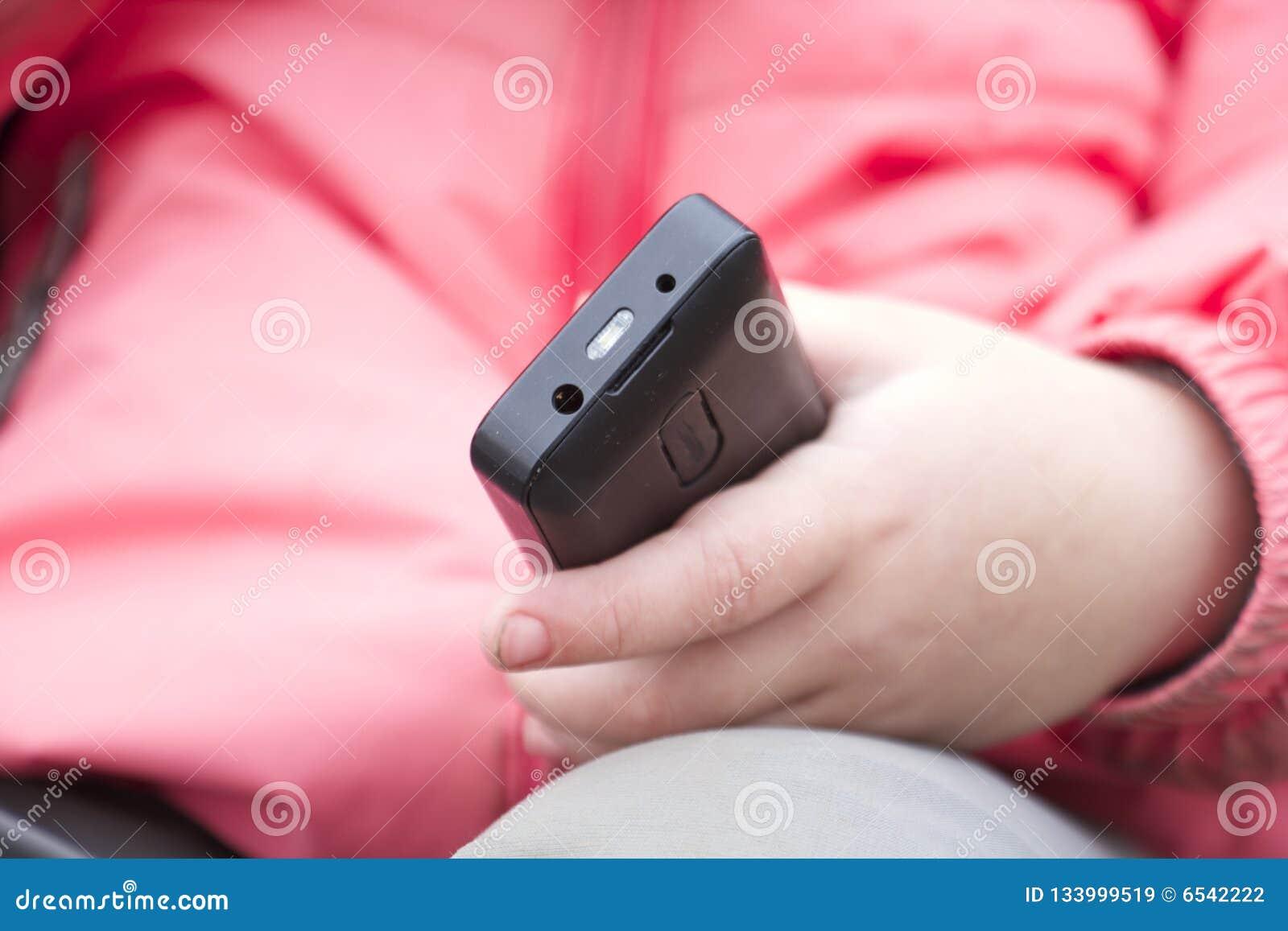 De hand van het kind met telefoon
