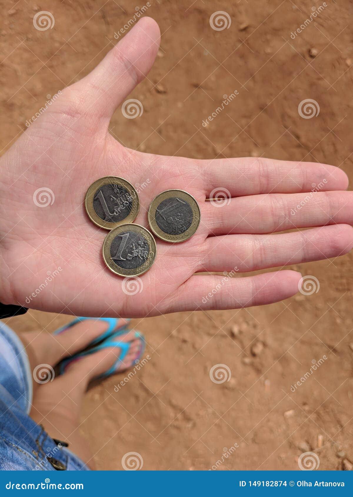 De hand van het meisje met drie euro in Cyprus