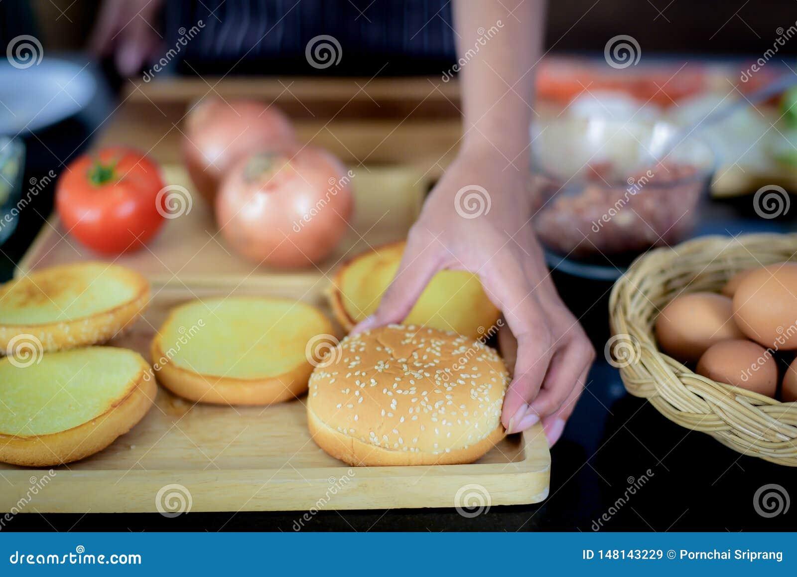 De hand van de kok plukt brood met sesamzaden op bovenkant Om in een pan worden gebakken voor ham het maken, die door ingredi?nte