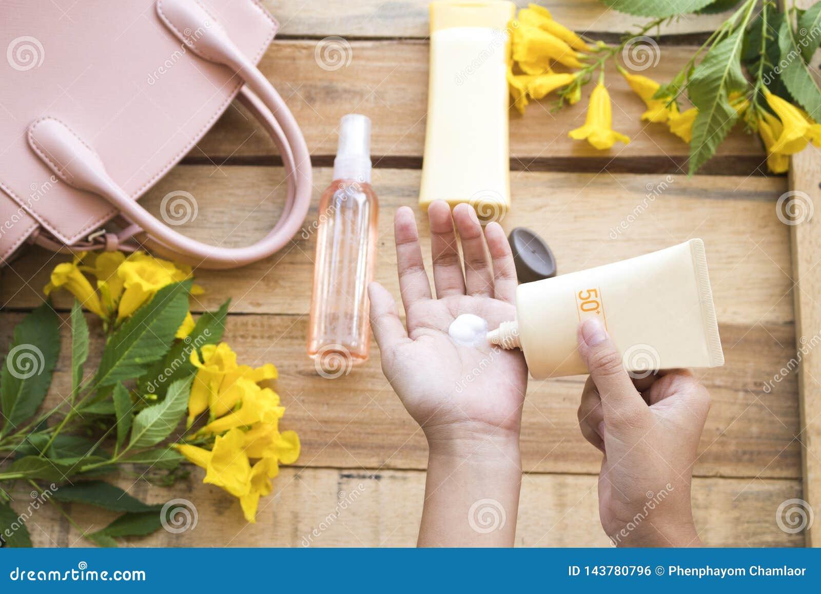 De hand van de roomzonnescherm spf50 van de meisjeshelling beschermt voor huidgezicht