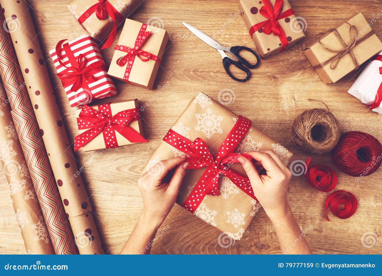 De hand van vrouw pakt dozen met Kerstmisgiften in