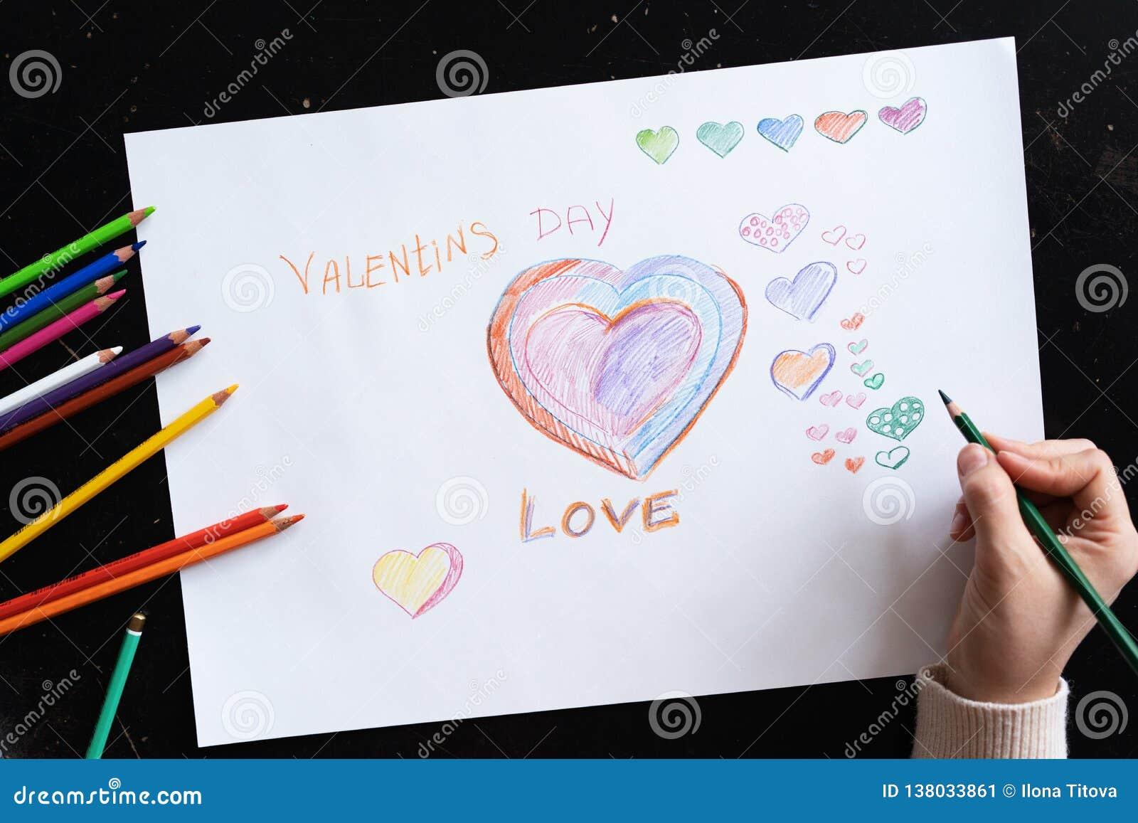 De hand van de vrouw trekt potlodenharten op papier voor de dag dichte omhooggaand van de valentijnskaart
