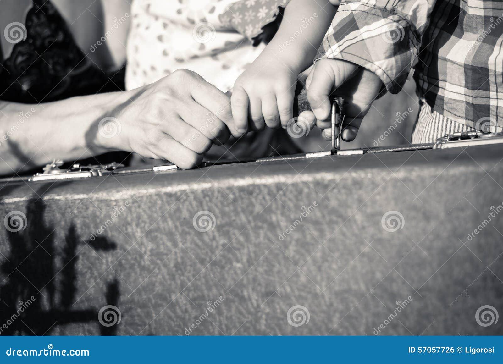 De handen die van de moeder en van twee jonge geitjes een handvat houden van