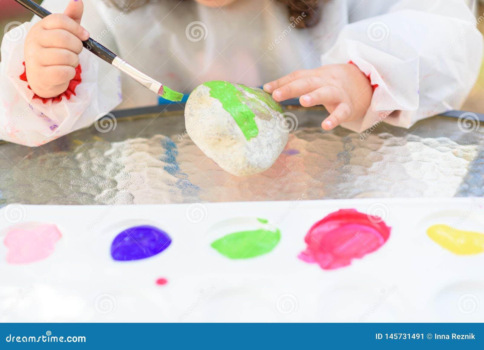 De handen die van het close-upkind door penseel en waterverf schilderen