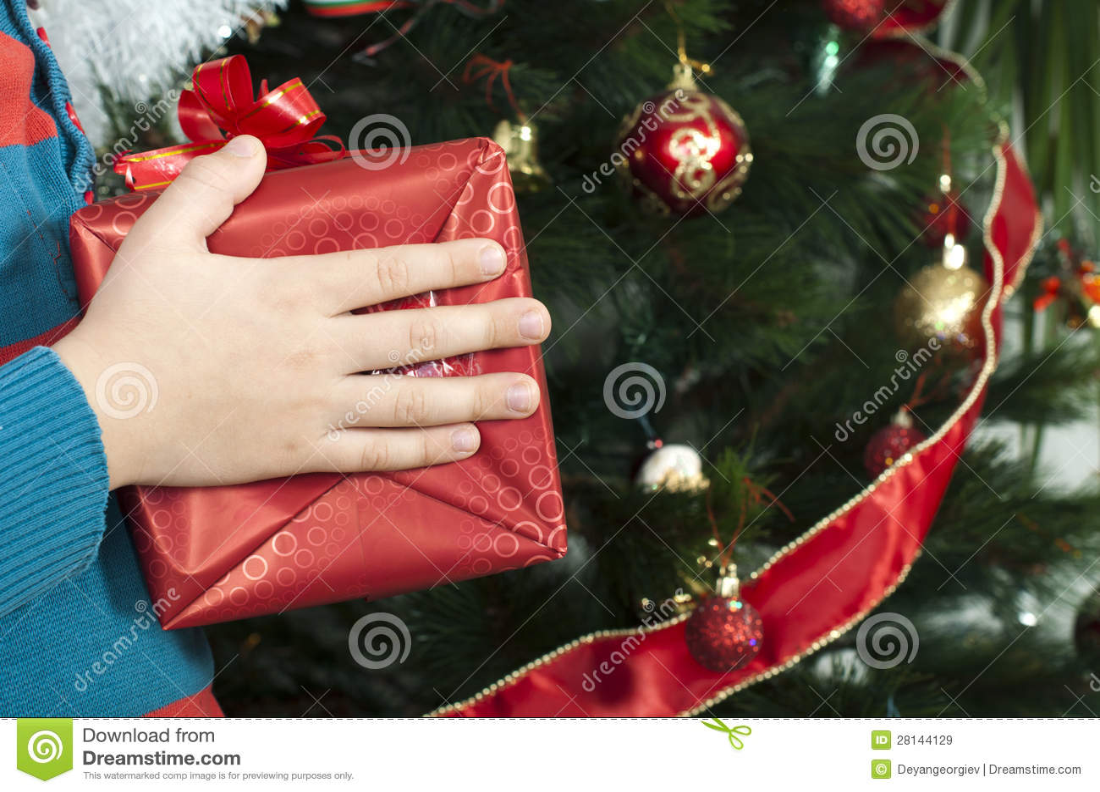 De handen die van kinderen Kerstmisgift houden