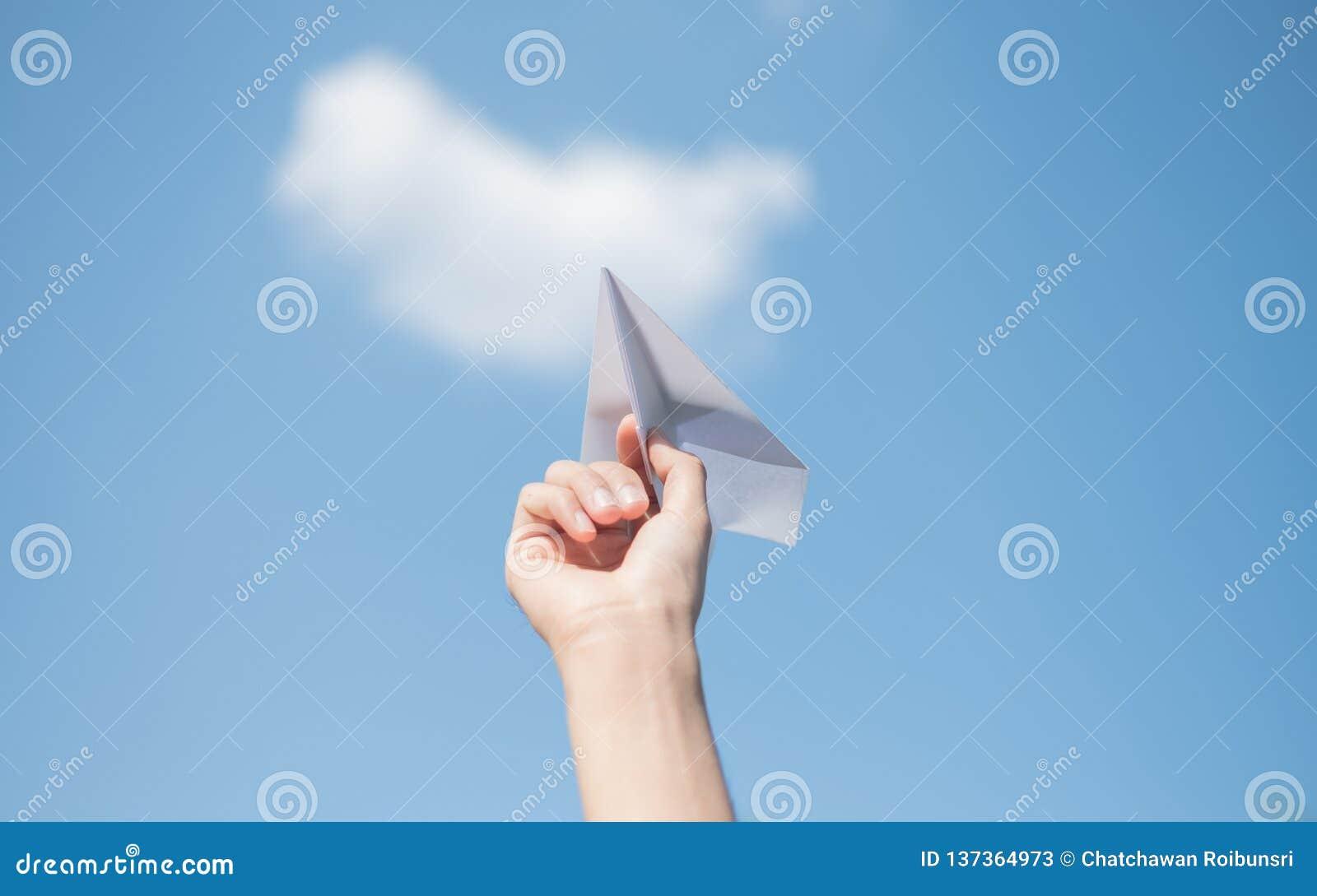 De handen die van mensen een Witboekraket met een heldere blauwe achtergrond houden