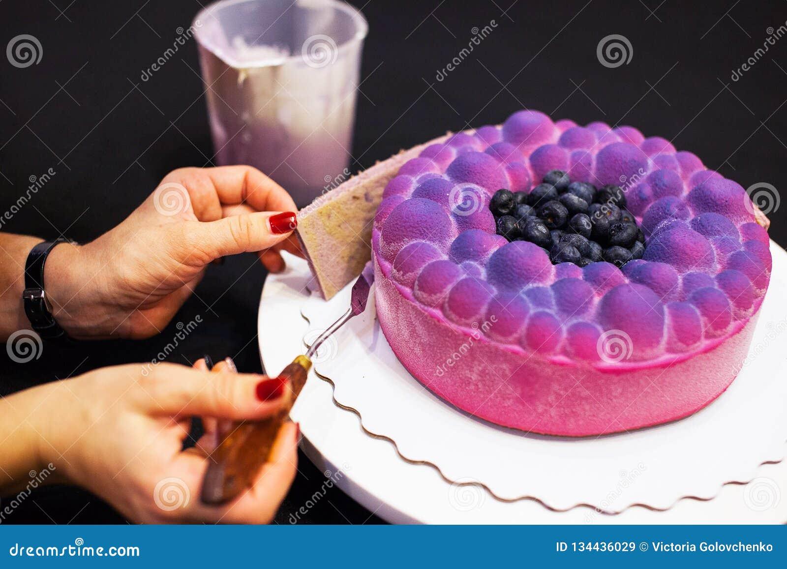 De handen die van de vrouw de cake van de moussebosbes verfraaien