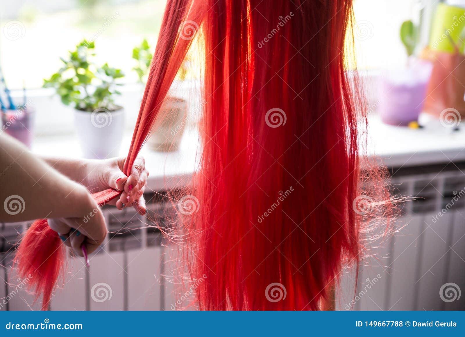 De handen die van de vrouw tactvol rood haar, slordige pruik op de tribune kammen