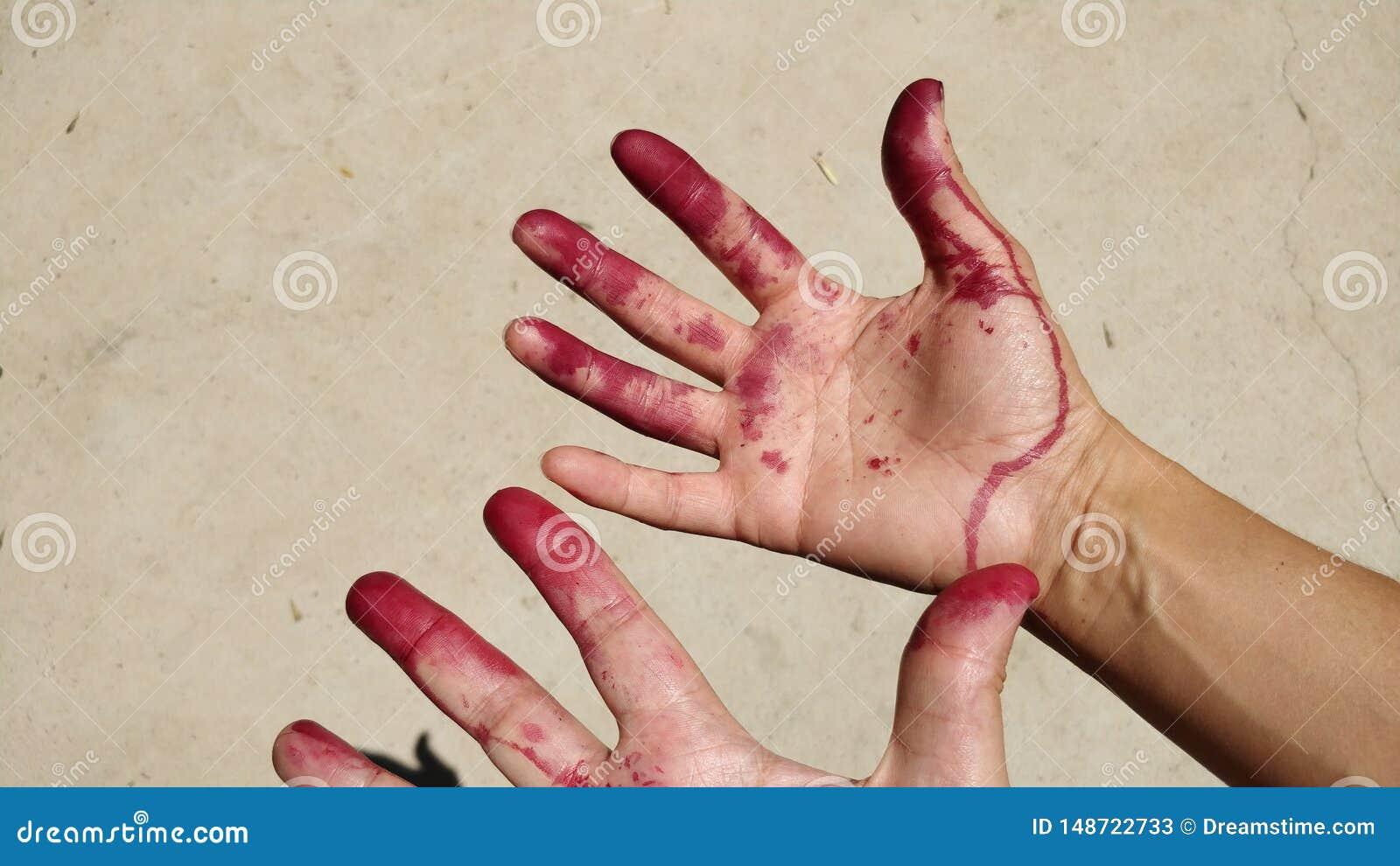 De handen en de vingers schilderden rood