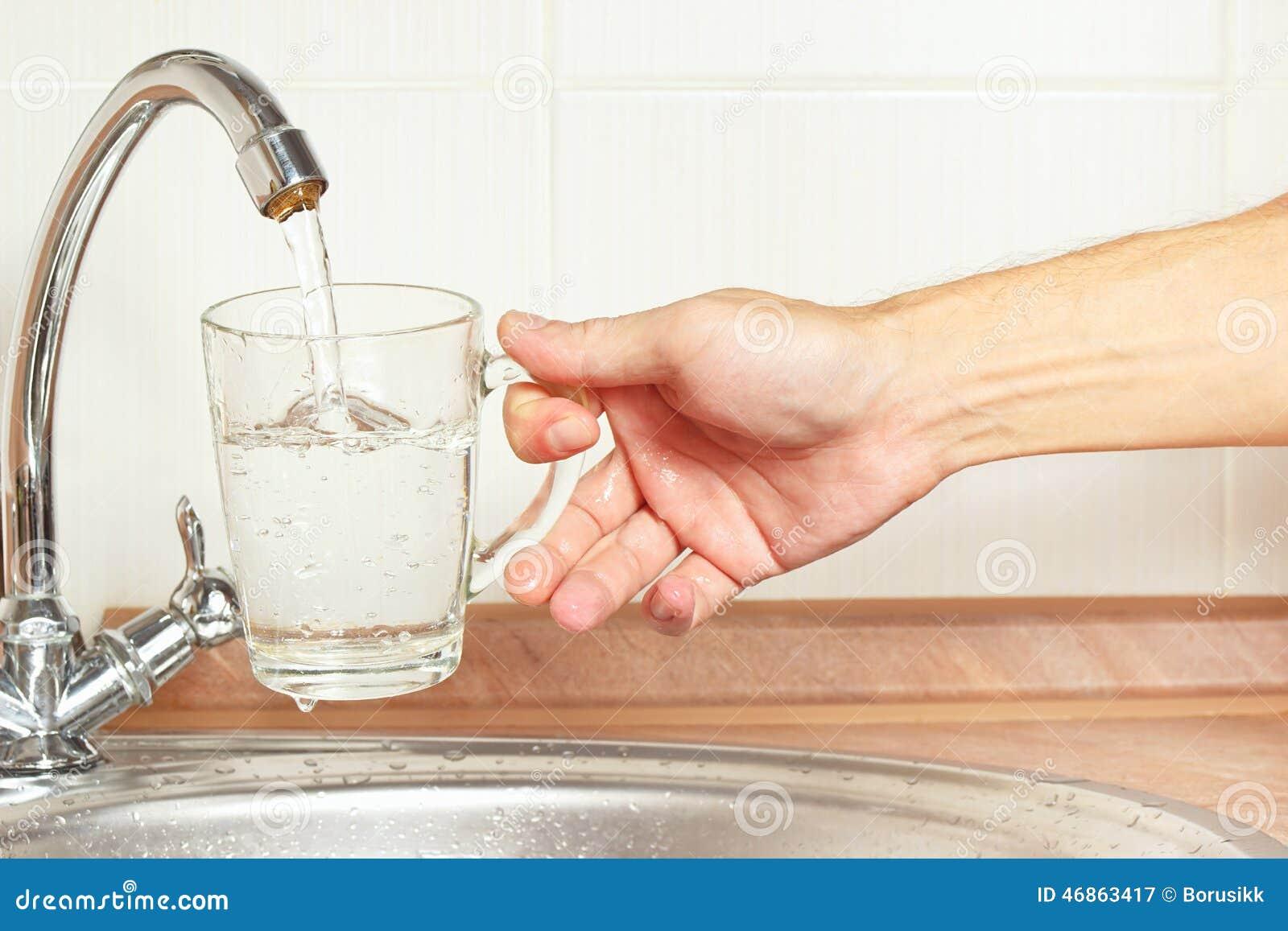 De handen gieten water in het glas onder de kraan in keuken stock
