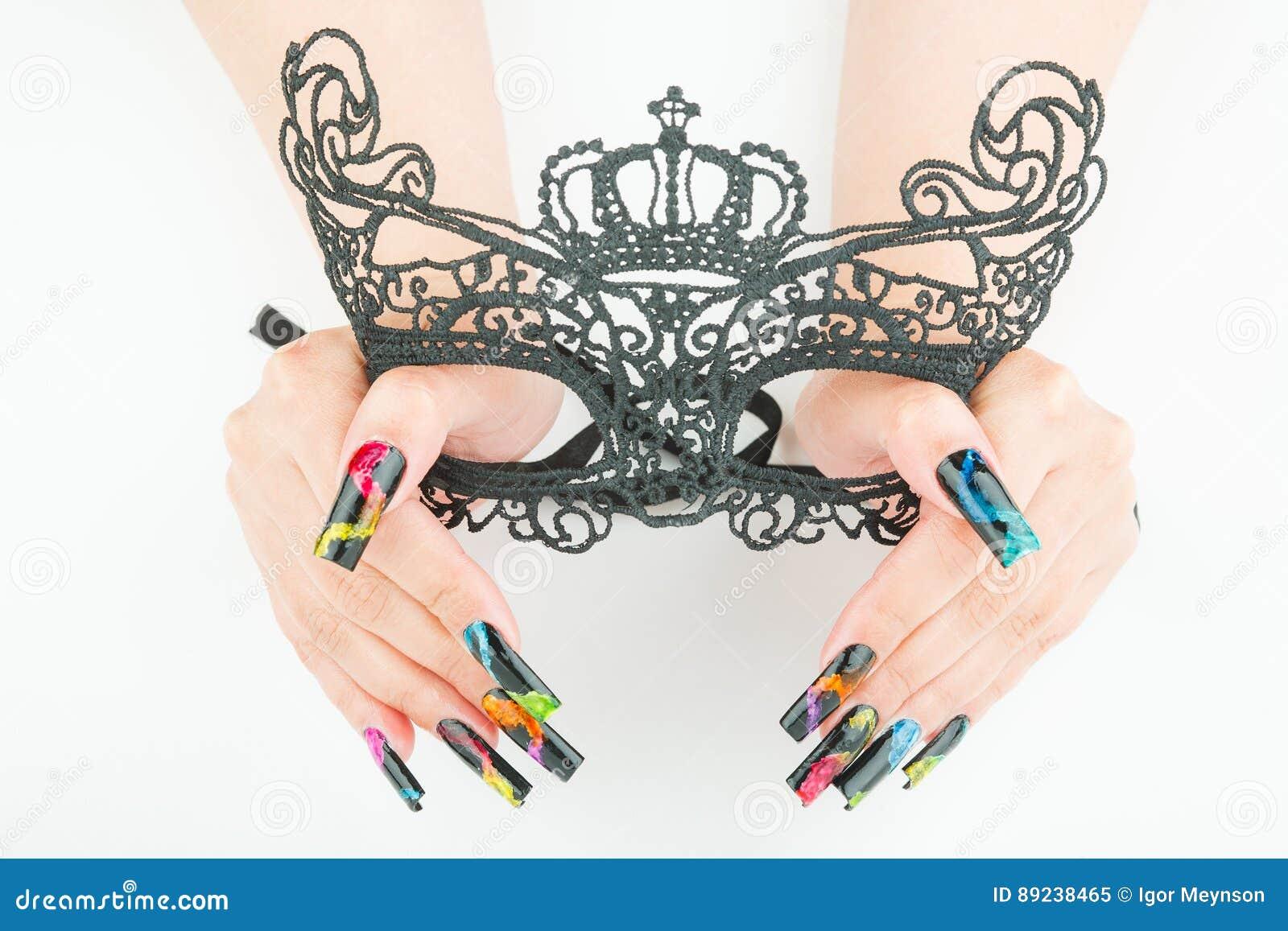 De handen met mooie manicure die een zwart kant Carnaval houden maskeren op witte achtergrond