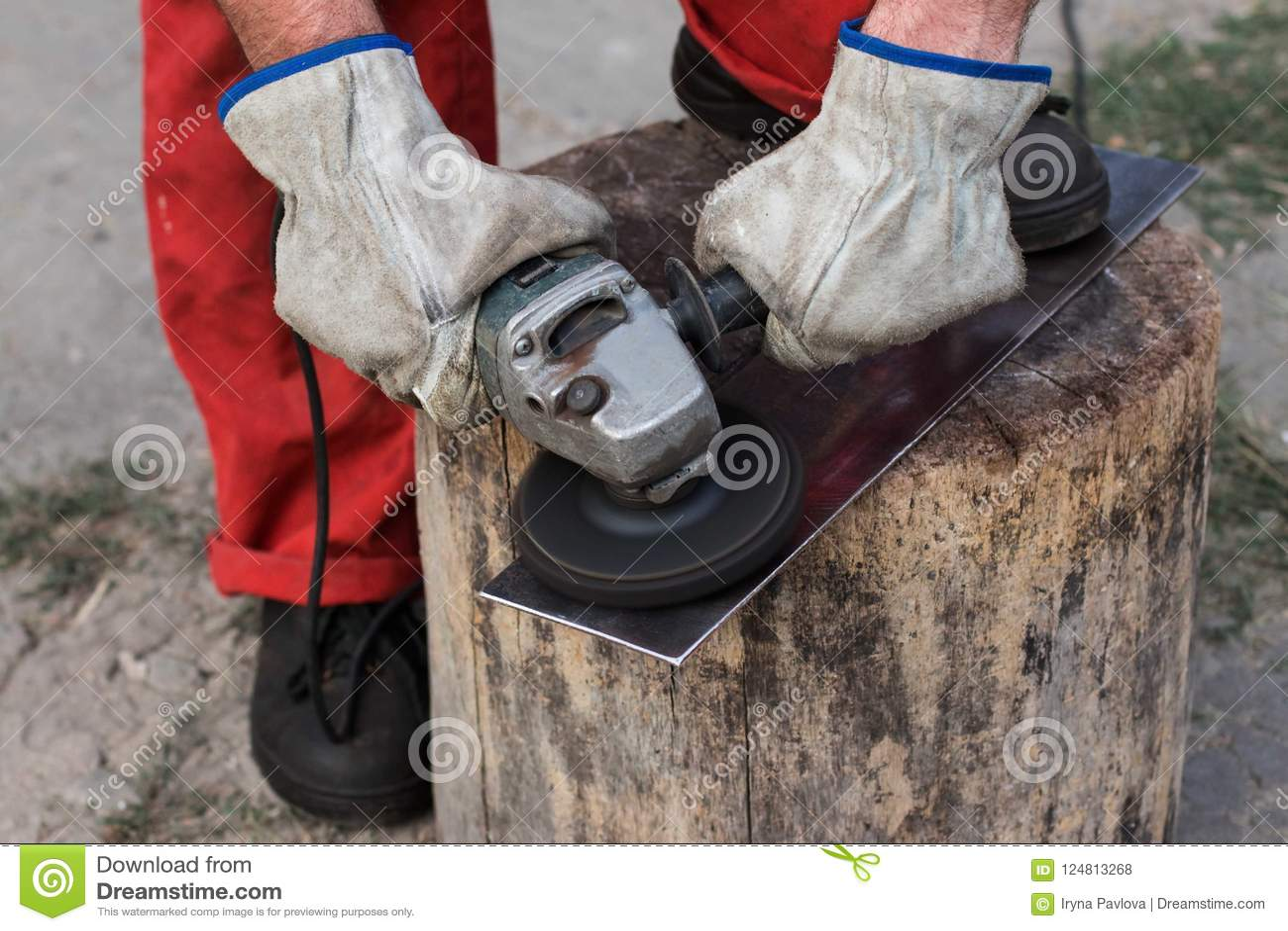 De handen van de arbeider in handschoenen behandelen een blad van metaal met een gri