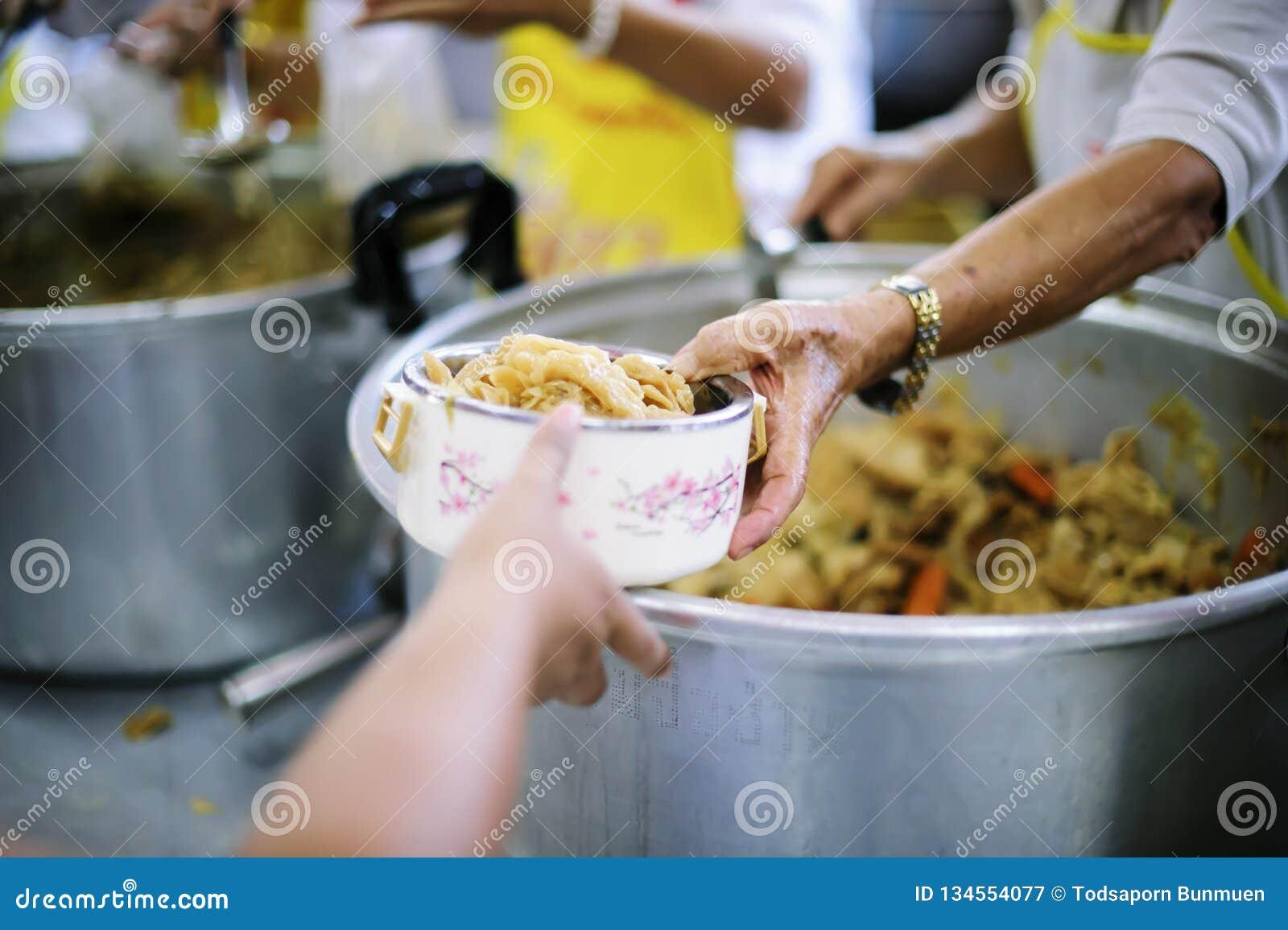 De handen van de armen wachten op voedselschenkingen om honger te verminderen: concept het voeden