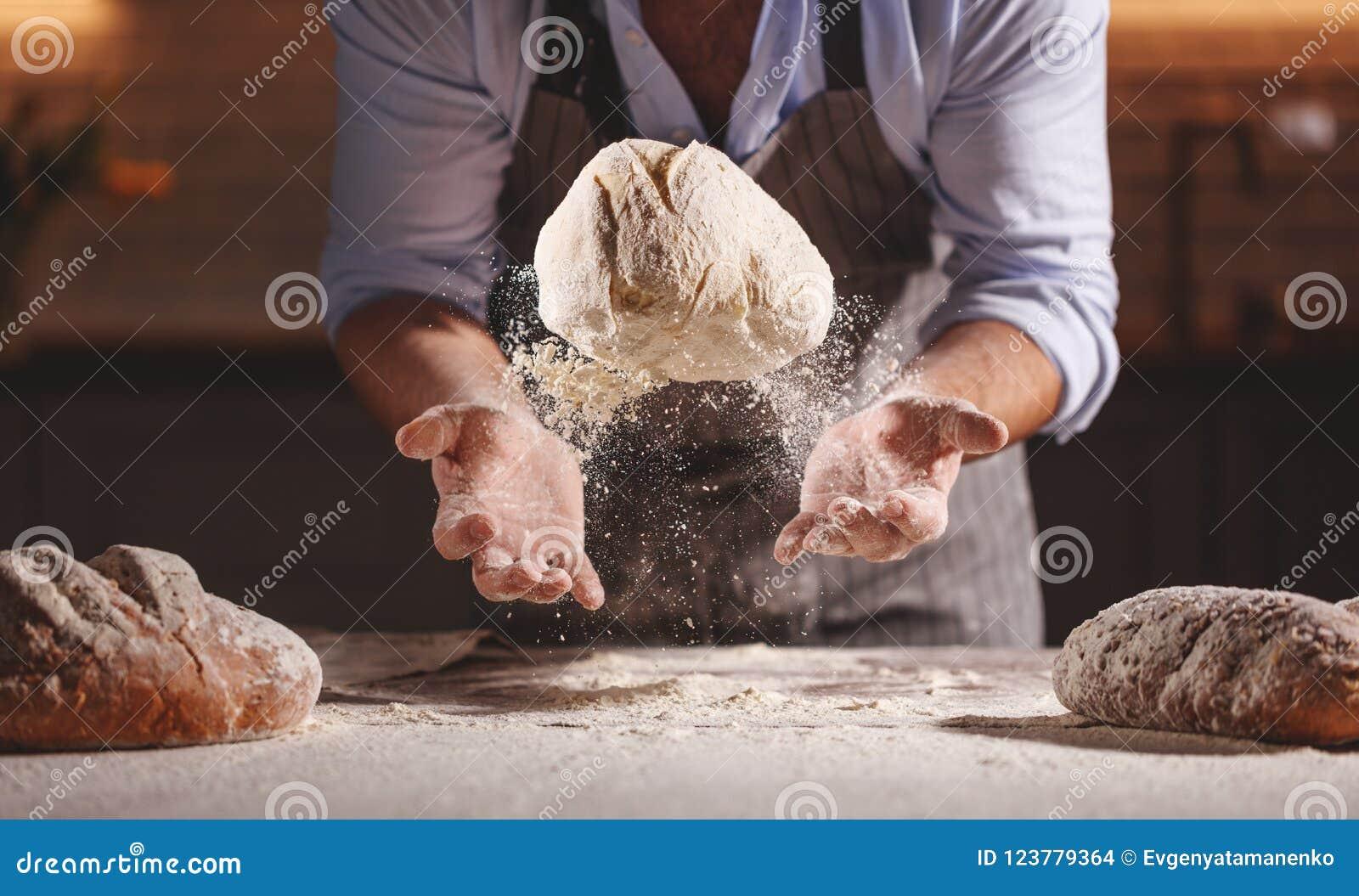 De handen van bakkers` s mannetje kneden deeg