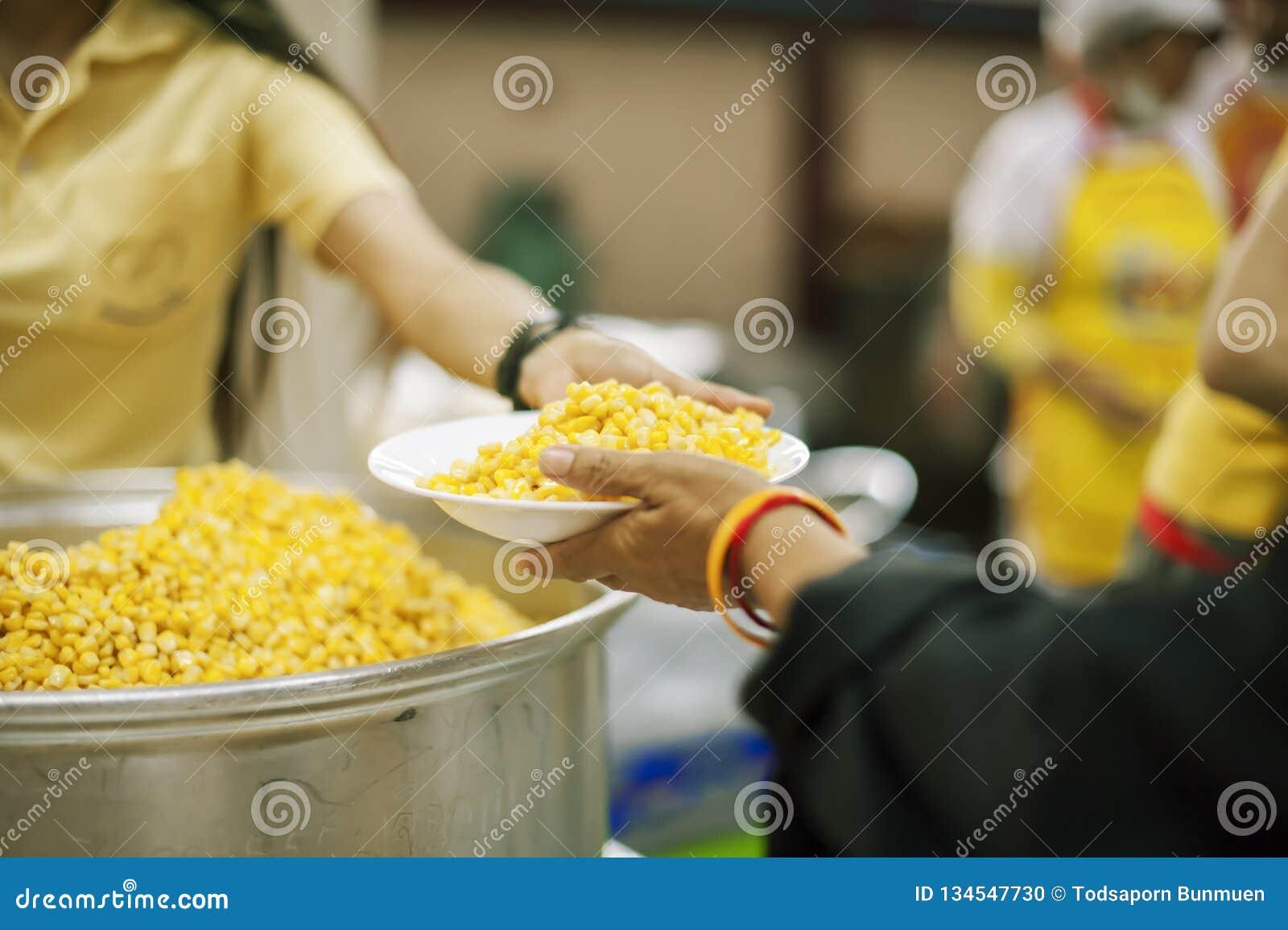 De handen van bedelaars ontvangen geschonken voedsel als aandeel in de maatschappij: het concept honger