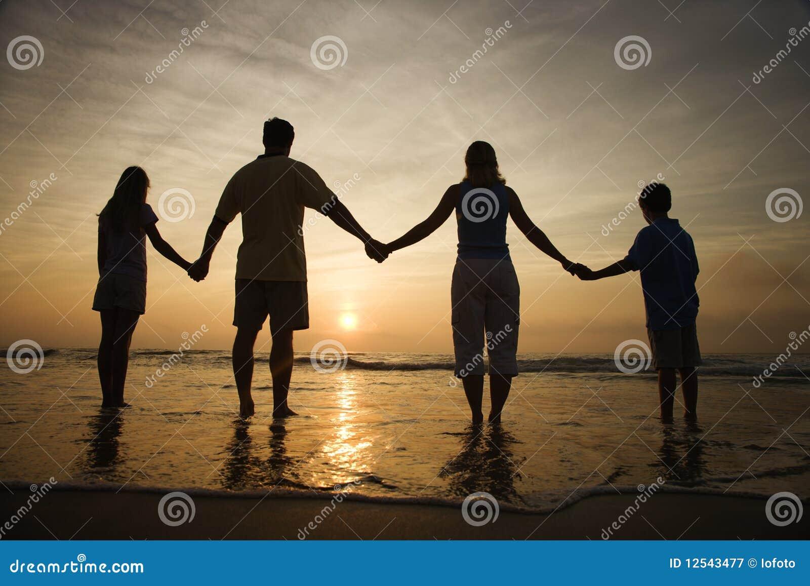 De Handen van de Holding van de familie op Strand dat op de Zonsondergang let
