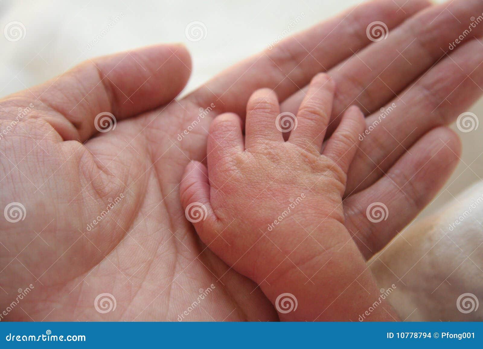 De handen van de moeder en van de baby