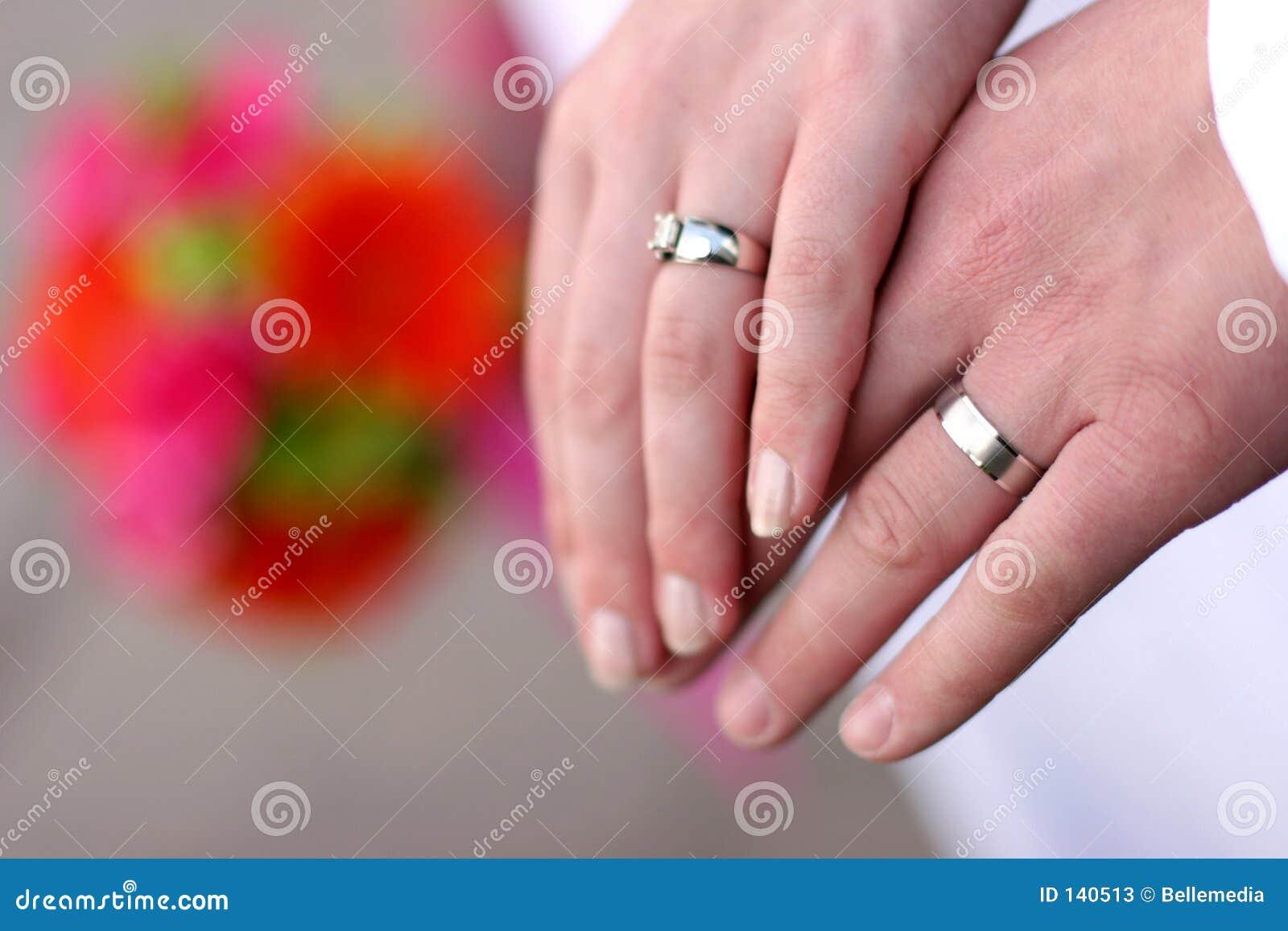 De handen van het paar van het huwelijk