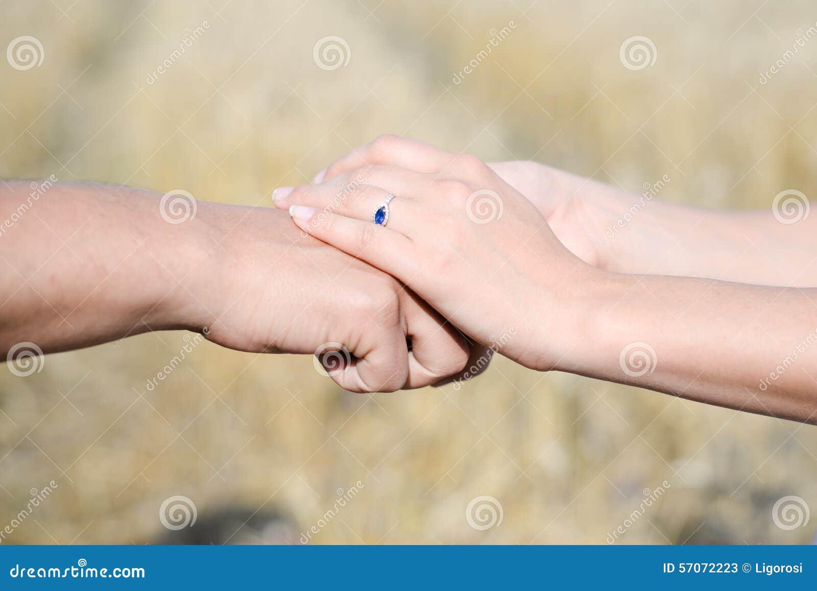 De handen van het wijfje gezet over de hand van het mannetje