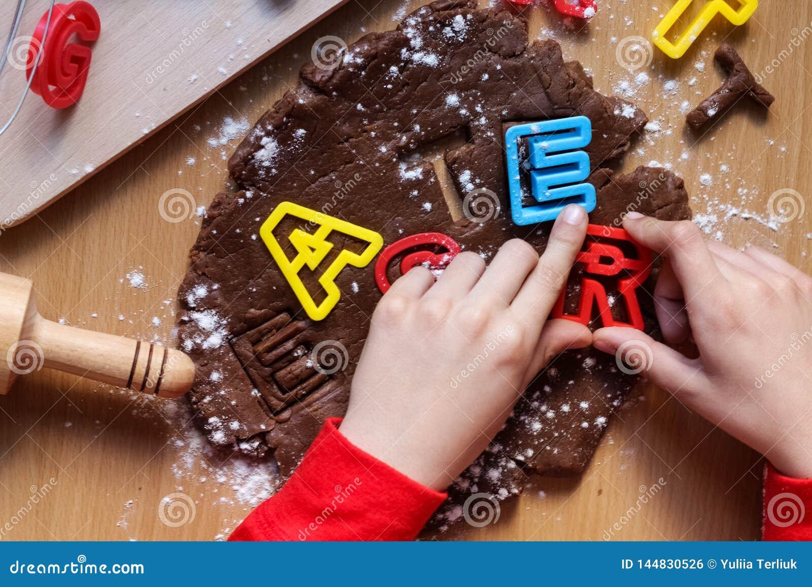 De handen van de jonge jongen snijden koekjes van ruw chocoladedeeg op een houten lijst met kleurrijke brieven Het koken traditio